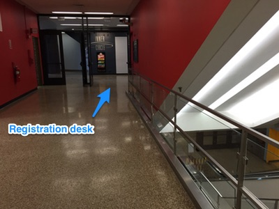 Turn left or right and head around the escalators to registration desk